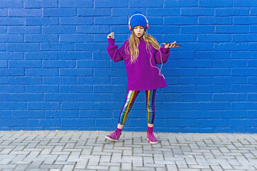 Girl wearing blue cap and oversized pink pullover listening music with headphones in front of blue wall - ERRF01210