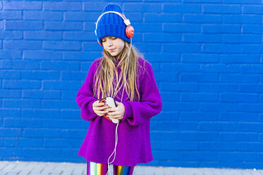 Girl wearing blue cap and oversized pink pullover listening music with headphones in front of blue wall - ERRF01213