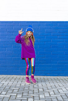 Girl wearing blue cap and oversized pink pullover listening music with headphones in front of blue wall - ERRF01216