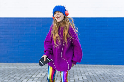 Portrait of happy girl singing while listening music with headphones and smartphone - ERRF01222