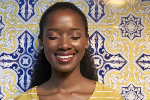 Portrait of a happy young woman at a tiled wall - VEGF00112