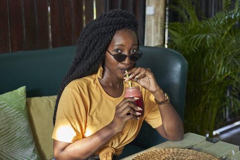 Rasta woman enjoying a smoothie in a café. CK Café, Moçambique, Maputo - VEGF00121
