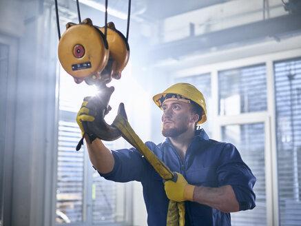 Industrial worker fixing hoist sling on indoor crane - CVF01121