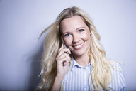 Portrait of smiling blond woman on the phone - MFRF01293