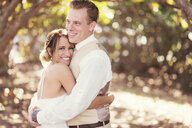 Caucasian bride and groom hugging outdoors - BLEF01861