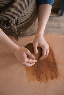 Hands of Caucasian woman rolling pottery clay - BLEF01864