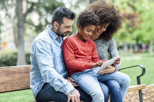 Family sitting on a park bench, using digital tablet - JSMF01055