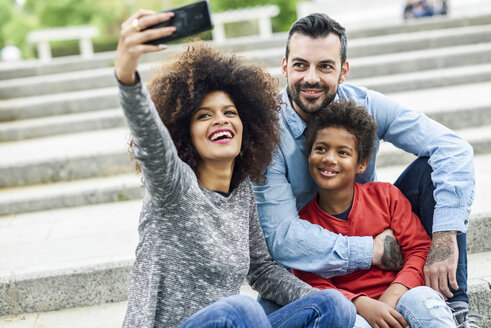Happy family taking selfies in a park - JSMF01058