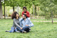Happy family sitting on grass in a park - JSMF01067