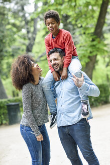 Happy family walking in a park, father carrying son piggyback - JSMF01073
