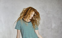 Portrait of redheaded young woman wearing striped t-shirt dancing - FMKF05660