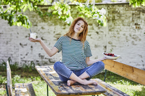 Portrait of young woman sitting on wooden table in garden holding bowl of berries and glass of yoghurt - FMKF05663