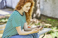 Smiling redheaded young woman  sitting on bench in the garden looking at cell phone - FMKF05669