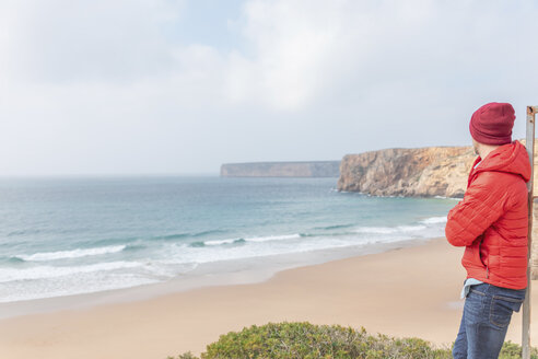Portugal, Algarve, Sagres, Praia do Beliche, man with red cap and jacket looking at the beach and sea - MMAF00883