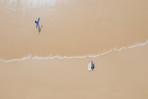 Portugal, Algarve, Sagres, Praia da Mareta, aerial view of two men with surfboards at the sea - MMAF00898