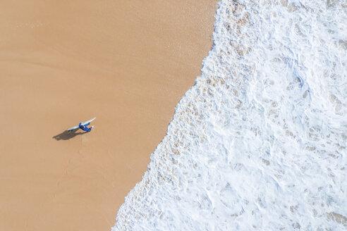 Portugal, Algarve, Sagres, Praia da Mareta, aerial view of man carrying surfboard on the beach - MMAF00901
