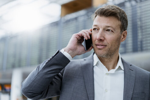 Portrait of businessman on cell phone at the airport - DIGF06838