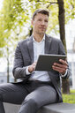 Businessman using tablet outside in the city - DIGF06844