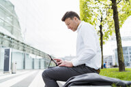 Businessman using tablet outside in the city - DIGF06847