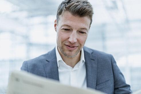 Portrait of businessman reading newspaper - DIGF06862