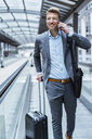 Smiling businessman with baggage and cell phone on moving walkway - DIGF06904