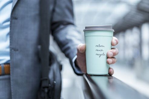Close-up of businessman holding recycable takeaway coffee cup - DIGF06910