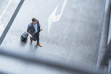 Top view of businessman walking with baggage and takeaway coffee - DIGF06913