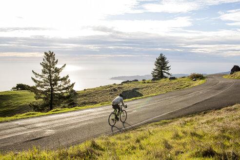 Caucasian man riding bicycle on road near ocean - BLEF02004