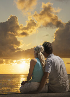 Caucasian couple admiring scenic view of sunset at ocean - BLEF02034