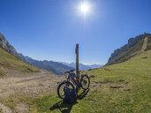 Spain, Asturia, Collada de Pelugano, E-Bike leaning on pole - LAF02277