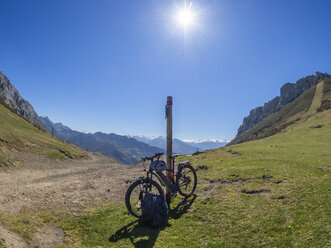 Spain, Asturia, Collada de Pelugano, E-Bike leaning on pole - LAF02277