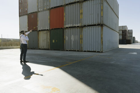 Manager talking on cell phone in front of cargo containers on industrial site - AHSF00219