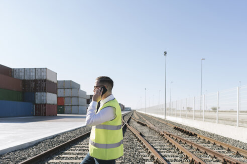 Man on railway tracks in front of cargo containers talking on cell phone - AHSF00222