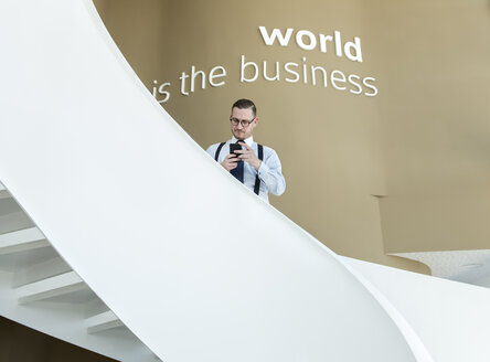 Businessman using cell phone on stairs in modern office - AHSF00246
