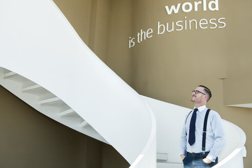 Confident businessman looking up stairs in modern office - AHSF00252