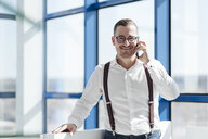Smiling businessman talking on cell phone at the window in modern office - AHSF00261