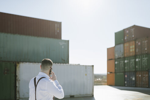 Rear view of manager talking on cell phone in front of cargo containers on industrial site - AHSF00273