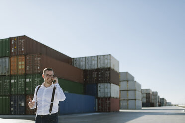 Manager talking on cell phone in front of cargo containers on industrial site - AHSF00276