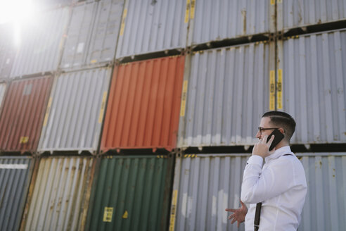 Manager talking on cell phone in front of cargo containers on industrial site - AHSF00279