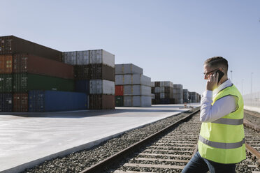 Man on railway tracks in front of cargo containers talking on cell phone - AHSF00285