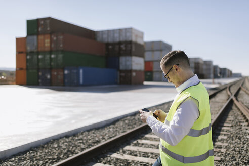Man on railway tracks in front of cargo containers using cell phone - AHSF00288