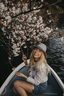 Japan, Tokio, Chidorigafuchi Park, smiling woman in rowing boat at cherry tree blossom - LHPF00708