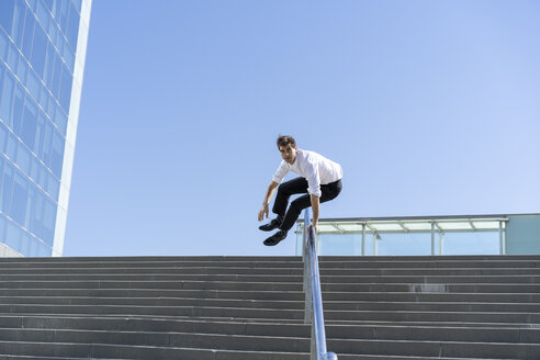 Businessman crossing banister in the city - AFVF02850