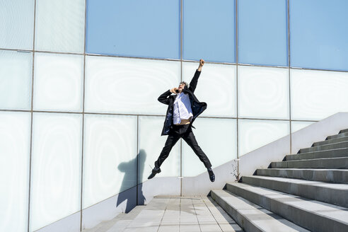 Excited businessman on cell phone jumping in the city - AFVF02862