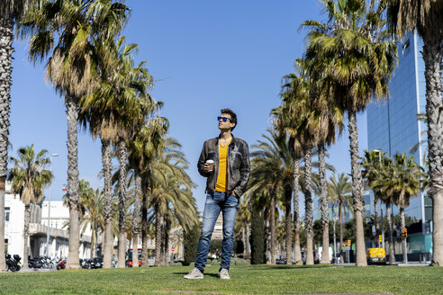 Spain, Barcelona, man standing on lawn in the city looking around - AFVF02877