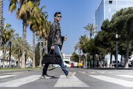 Spain, Barcelona, man in the city crossing the street - AFVF02880