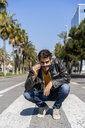 Spain, Barcelona, man crouching on zebra crossing - AFVF02886