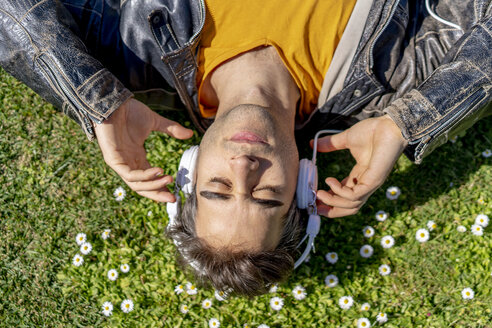 Man lying on flower meadow with headphones - AFVF02889