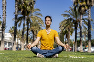 Spain, Barcelona, man practicing yoga on lawn in the city - AFVF02895