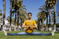 Spain, Barcelona, man practicing yoga on lawn in the city - AFVF02898